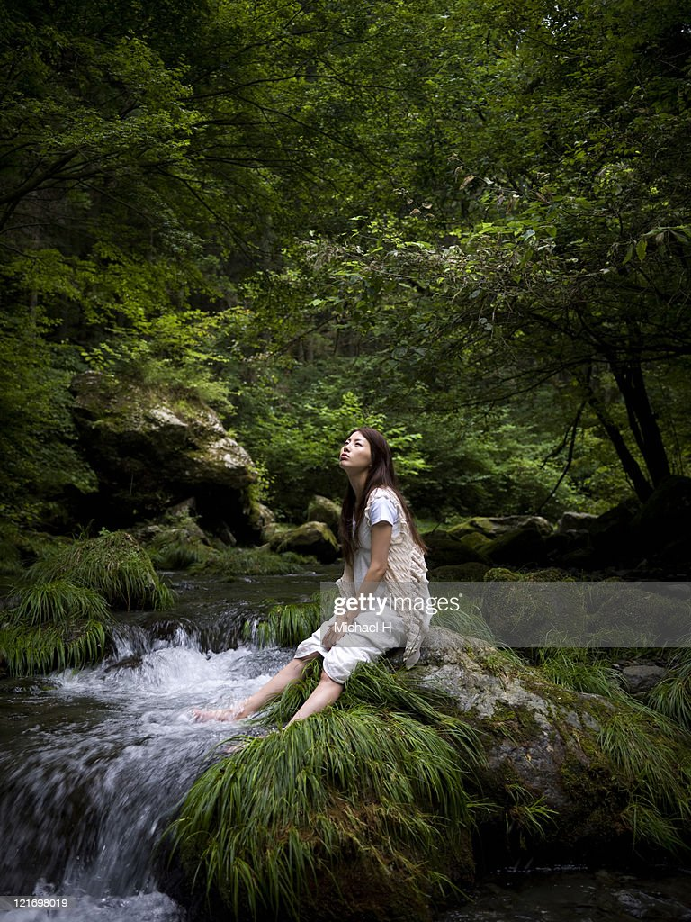 Woman who is relaxing near beautiful brooklet : Stock Photo