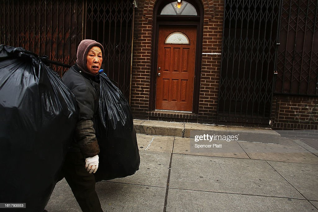 A woman who makes a living by collecting bottles and cans or 'canning' for short, carries an evenings collection into Sure We Can, a non-profit bottle redemption center in Bushwick, Brooklyn that is pushing to become a cooperative for the canning community on February 16, 2013 in New York City. Sure We Can, which was partly started by homeless canners in 2007 and is run by one of its founders Sister Ana Martinez de Luco, looks to give the diverse members of the canning community a safe and fraternal place to redeem cans, store their carriages and become members of an association that encourages self-dependence and responsibility. Many of New York's canners are non-English-speaking elderly immigrants who live a marginalized existence and are vulnerable to dishonest business practices. Sure We Can currently serves around 50 canners per day and recycles over 6 million bottles and cans per year.