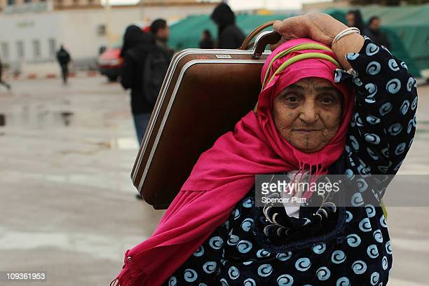 A woman who recently fled Libya walks with her luggage on the Tunisian side of the border on February 23 2011 in Jdir Tunisia As fighting continues...
