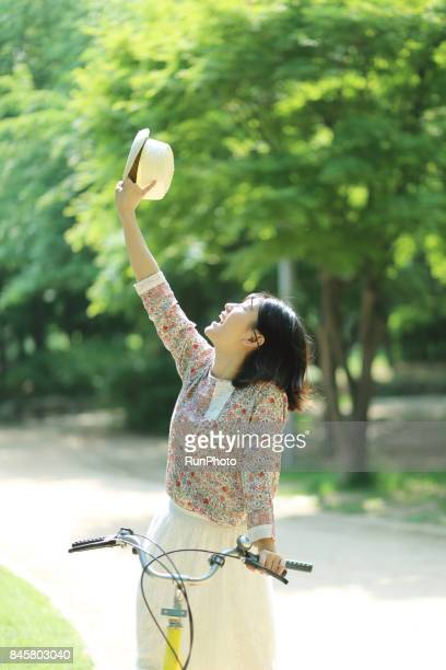 woman who rides a bicycle in a park and enjoys a hat