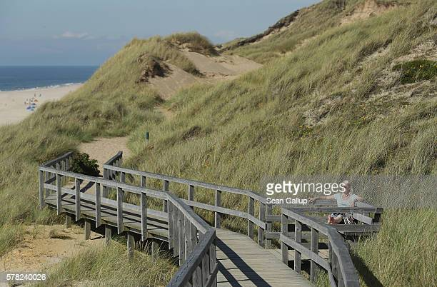 A woman who said she did not mind being photographed relaxes on a wooden walkway on a trail that runs along dunes at a beach on Sylt Island on July...