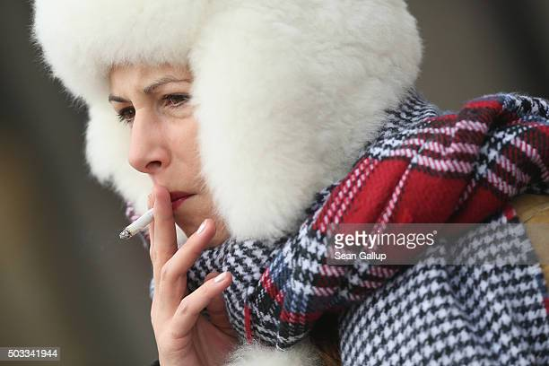 A woman who said she did not mind being photographed smokes a cigarette as she stands bundled against the cold at a crosswalk in the city center on...