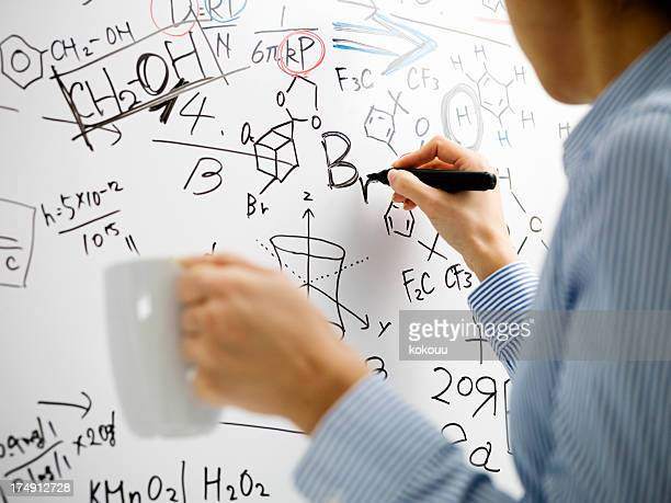 Woman who writes a formula to white board