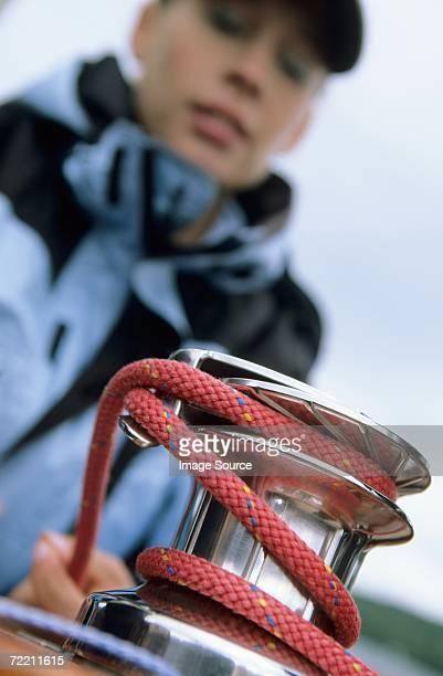 Woman winding rope around crank