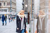 Beautiful young woman window shopping in historical centre of the city of Vienna, Austria. Winter.