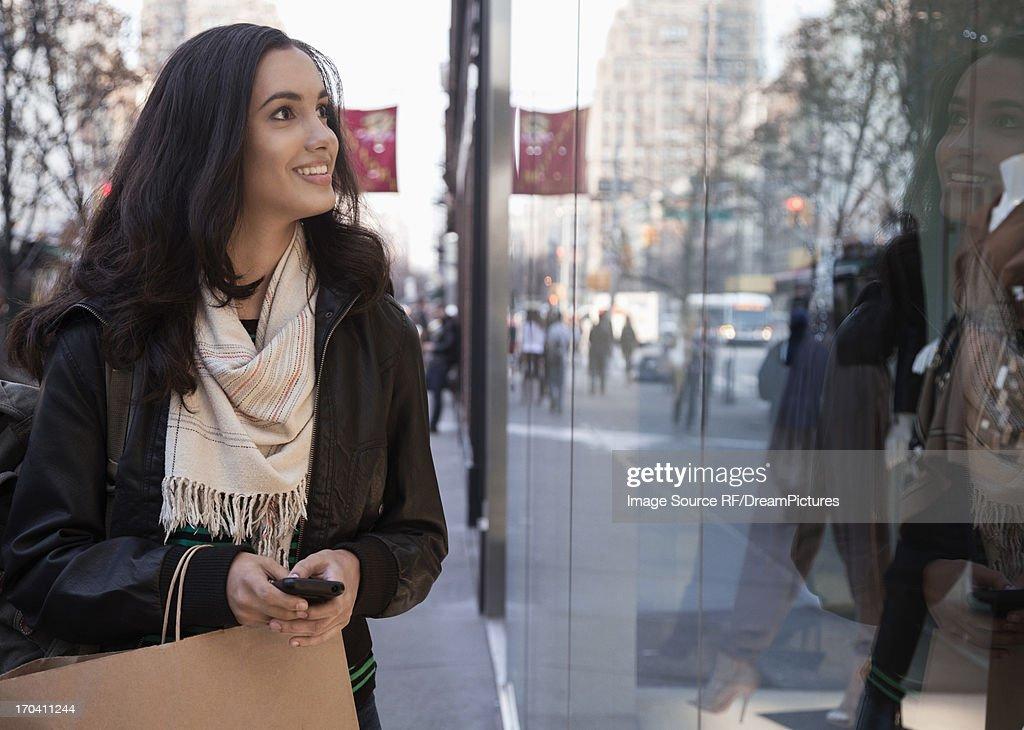 Woman window shopping on city street : Stock Photo