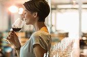 Woman wine tasting red wine in winery tasting room