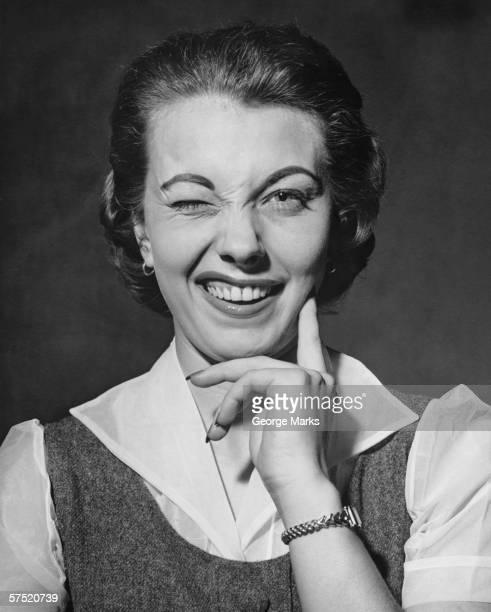 Woman winking in studio, (B&W), portrait