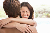 Smiling young woman winking while embracing man