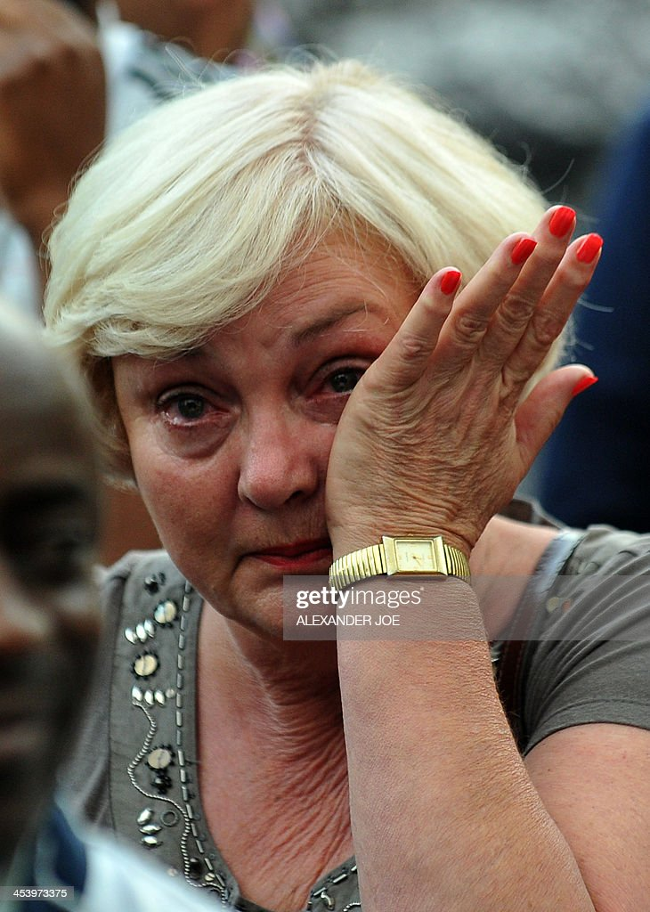 A woman wipes a tear during n ANC party meeting outside the home of South African president Nelson Mandela in Johannesburg on December 6, 2013 where he died the day before. Mandela, the revered icon of the anti-apartheid struggle in South Africa and one of the towering political figures of the 20th century, has died aged 95. Mandela, who was elected South Africa's first black president after spending nearly three decades in prison, had been receiving treatment for a lung infection at his Johannesburg home since September, after three months in hospital in a critical state.