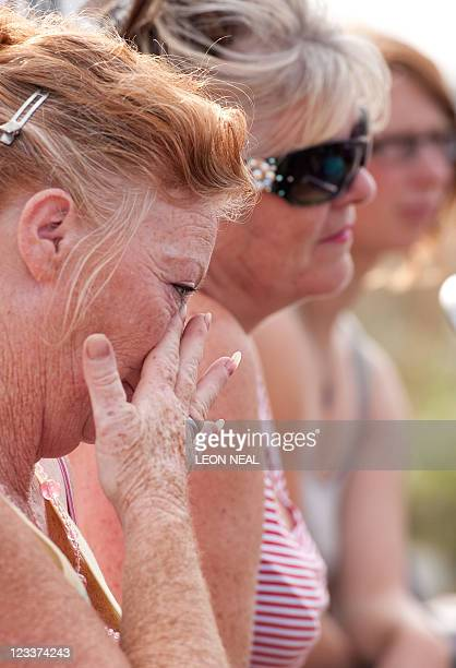 A woman wipes a tear from her eye as residents of the Dale Farm travellers' site near Basildon in Essex south east England speak to members of the...