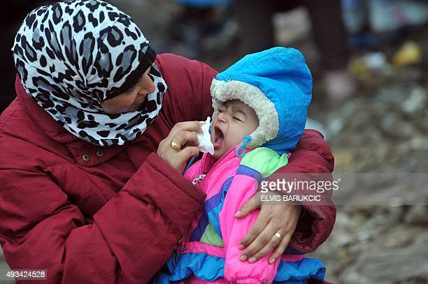 A woman wipes her baby's face as she waits under the rain with other migrants and refugees to cross the SerbianCroatian border in the village of...