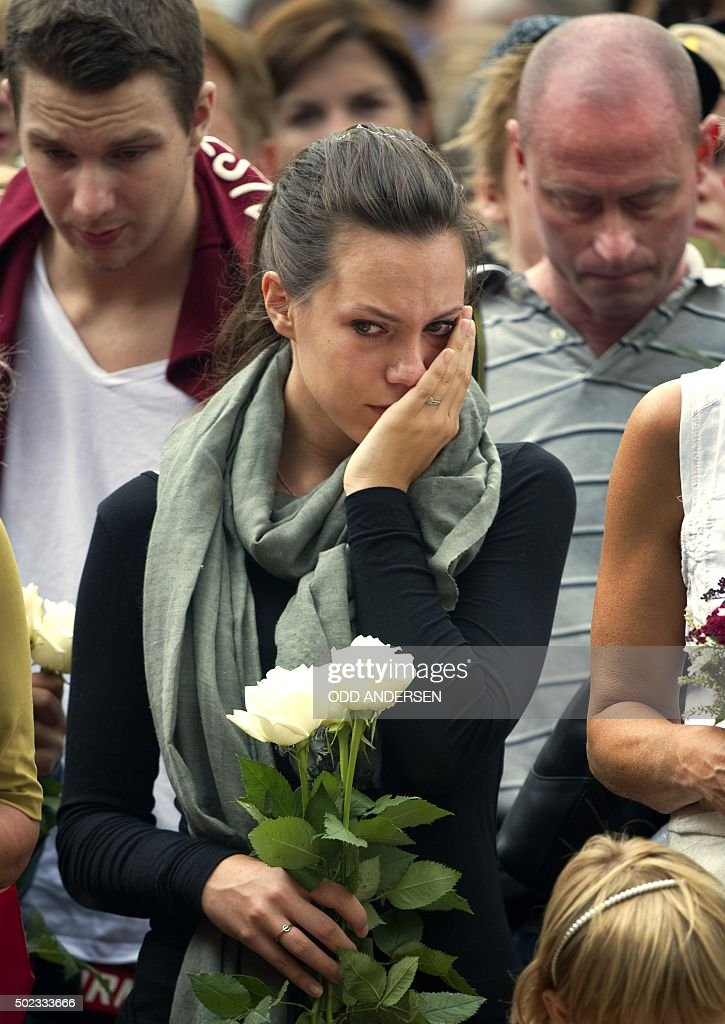A woman wipes her face during a gathering on July 24 2011 in Oslo to pay tribute to the victims of a bomb explosion which ripped through government...