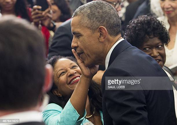 A woman wipes her lipstick off the check of US President Barack Obama after kissing him as he greets people after speaking at Lawson State Community...