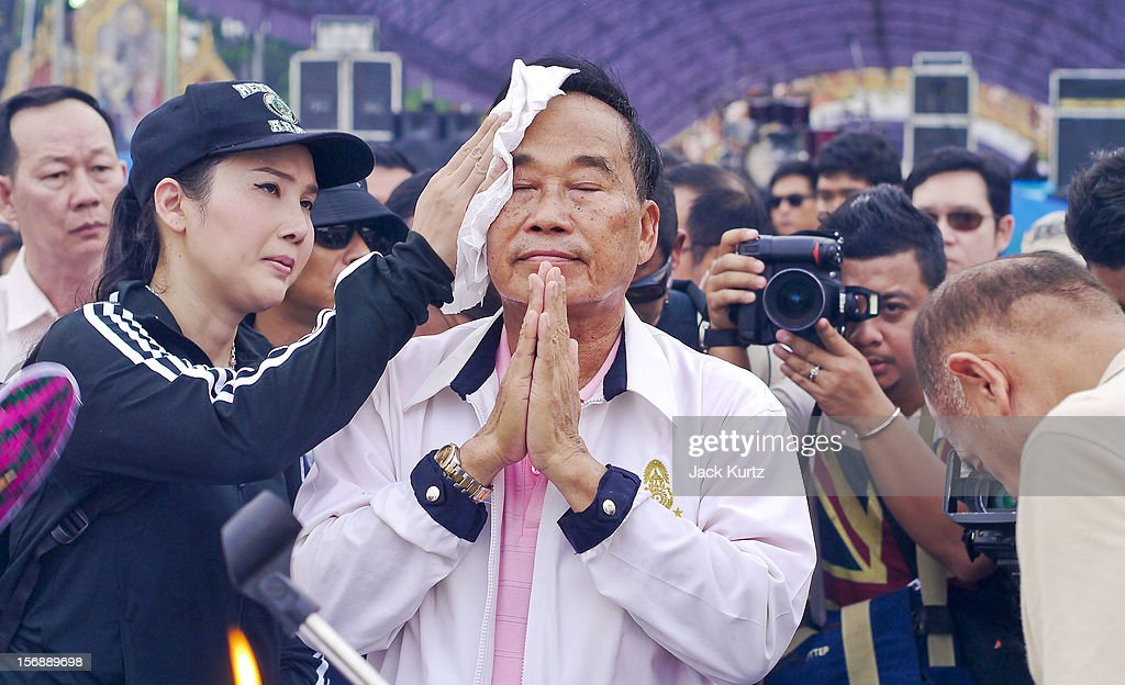 A woman wipes sweat from his brow while Gen Boonlert 'Seh Ai' KaewprasitÊleader of Pitak Siam, participates in a Brahmin blessing ceremony during a large anti government protest on November 24, 2012 in Bangkok, Thailand. The Siam Pitak group, which sponsored the protest, cited alleged government corruption and anti-monarchist elements within the ruling party as grounds for the protest. Police used tear gas and baton charges againt protesters.