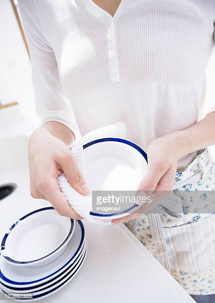 A woman wiping a dish