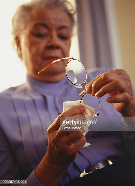 Woman wiping spectacles, low angle view