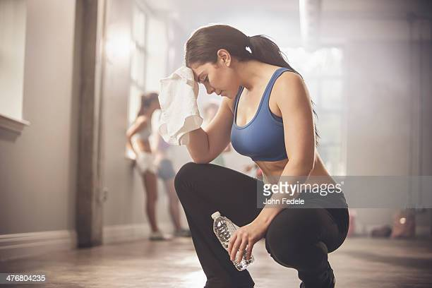 Woman wiping sweat with towel in gym