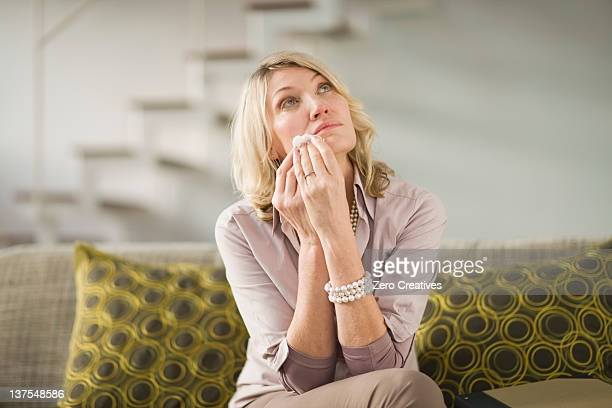 Woman wiping tears from cheeks