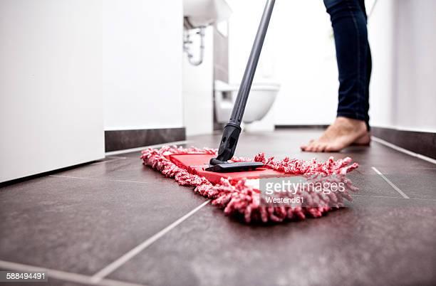 Woman wiping the floor in bathroom