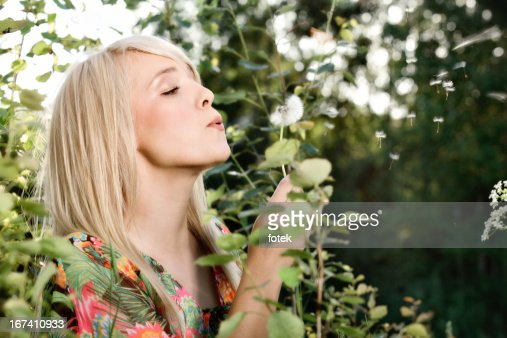Woman wishing on a dandelion : Stockfoto