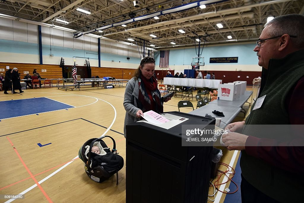 A woman with a baby casts her ballot for the first US presidential primary at a school gym in Concord, New Hampshire, on February 9, 2016. New Hampshire voters headed to polls at the snowy break of day on February 9 for the crucial first US presidential primary, with Donald Trump chasing victory and Hillary Clinton looking to narrow the gap on Bernie Sanders. The northeastern state, home to just 1.3 million people, sets the tone for the primaries -- and could shake out a crowded Republican field as the arch-conservative Senator Ted Cruz and establishment candidates led by Marco Rubio battle for second place behind the frontrunner Trump. / AFP / Jewel Samad