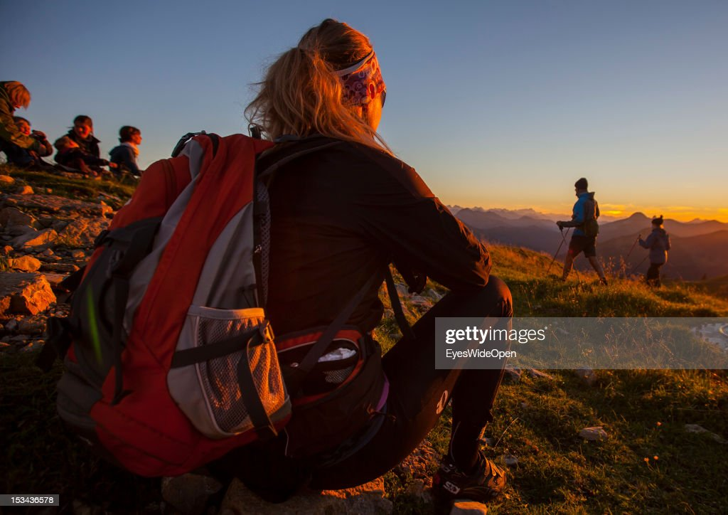 A woman with a backpack and hikers are watching the sunset at the mountain of Rotwand with a panoramic view of the so called Blue Bavarian Alps on August 29, 2012 in Spitzingsee, Bavaria, Germany.