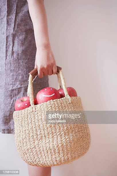 A woman with a basket containing apple.