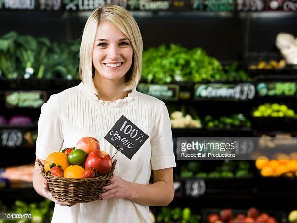 Mujer con una canasta de frutas orgánicos