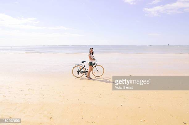 Woman with a bicycle on the beach in summer