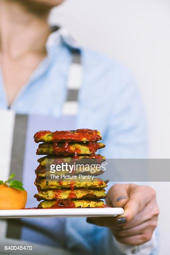 A woman with a blue shirt and striped apron serving leek fritters with chili sauce on a white marble board.