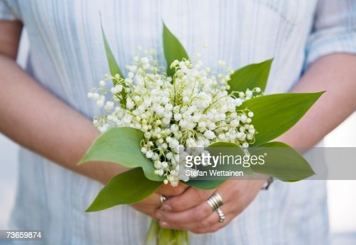 Woman with a bouquet of lilies of the valley.