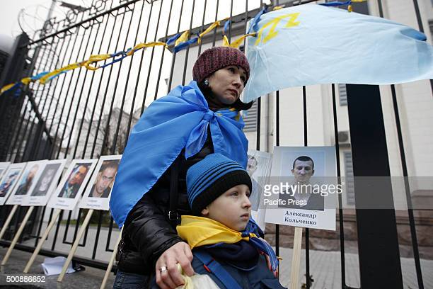 A woman with a boy stands near portraits of the dead and repressed activists in front of the Russian embassyduring a protest of Crimean Tatars and...