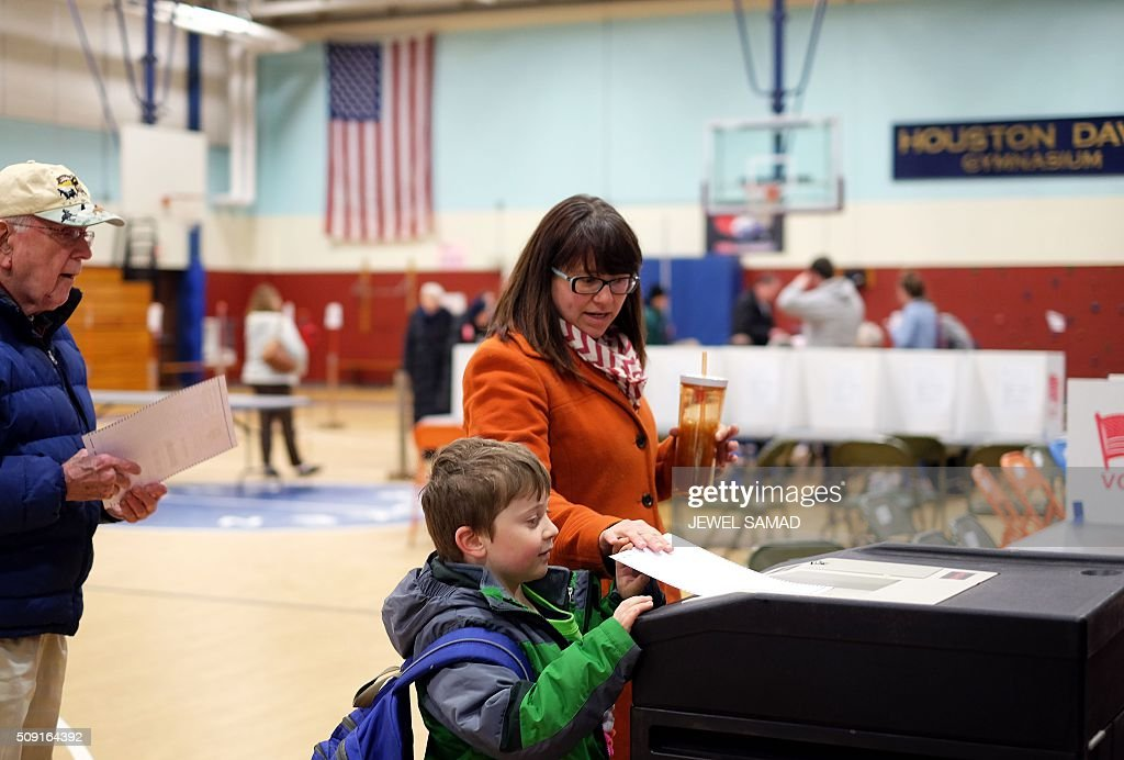 A woman with a child casts her ballot for the first US presidential primary at a school gym in Concord, New Hampshire, on February 9, 2016. New Hampshire voters headed to polls at the snowy break of day on February 9 for the crucial first US presidential primary, with Donald Trump chasing victory and Hillary Clinton looking to narrow the gap on Bernie Sanders. The northeastern state, home to just 1.3 million people, sets the tone for the primaries -- and could shake out a crowded Republican field as the arch-conservative Senator Ted Cruz and establishment candidates led by Marco Rubio battle for second place behind the frontrunner Trump. / AFP / Jewel Samad