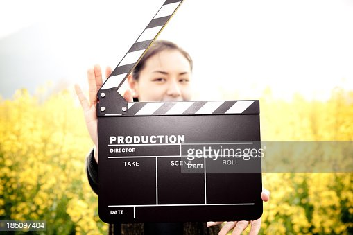 A woman with a clapper board outside