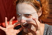 Redhead woman with a cosmetic mask on her face