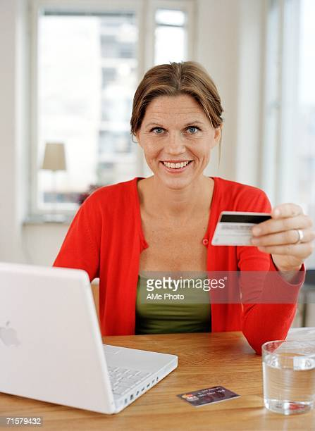 A woman with a credit card by a computer.