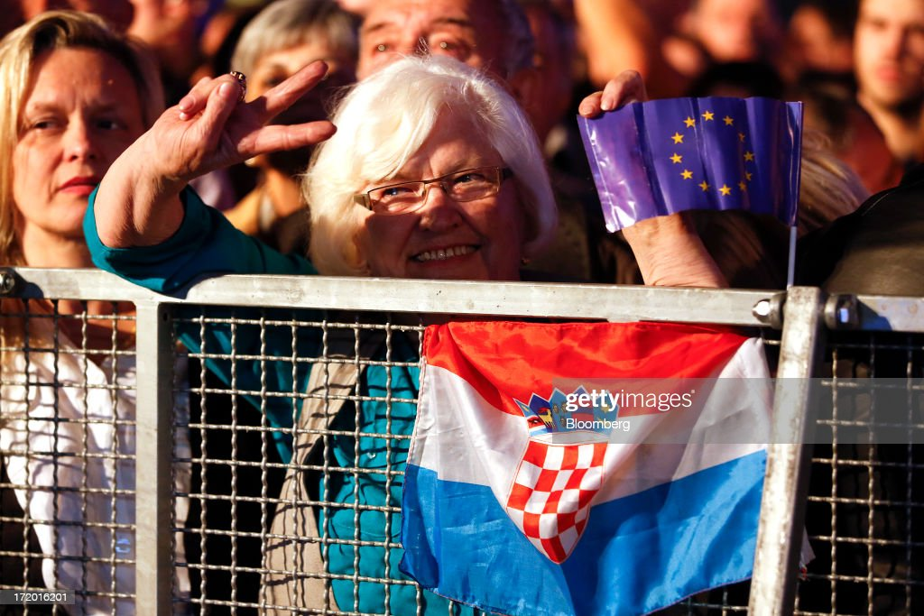 A woman with a Croatian national flag and European Union (EU) flag stands in Ban Jelacic square and celebrates as Croatia marks it's entry into the European Union (EU) in Zagreb, Croatia, on Sunday, June 30, 2013. Croatia will become the European Union's 28th member at midnight, the bloc's first addition since Bulgaria and Romania joined in 2007. Photographer: Simon Dawson/Bloomberg via Getty Images