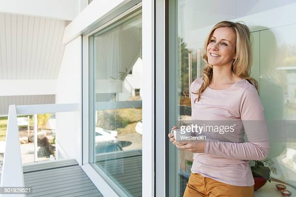 Woman with a cup of coffee leaning at glass front of her house