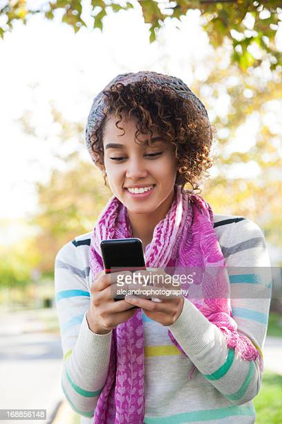 A woman with a curly hair wearing a pink scarf texting