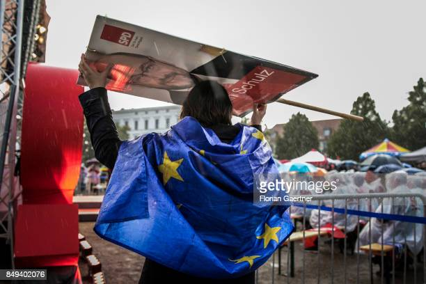 A woman with a flag of the European Union is protected by an election poster of the candidate for the german chancellorship of the Social Democratic...