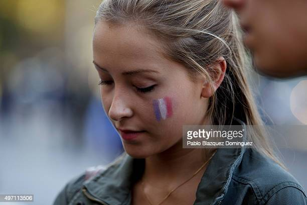 A woman with a French flag painted on her face looks down before a minute of silence in tribute to the victims of yesterday's Paris attacks out...