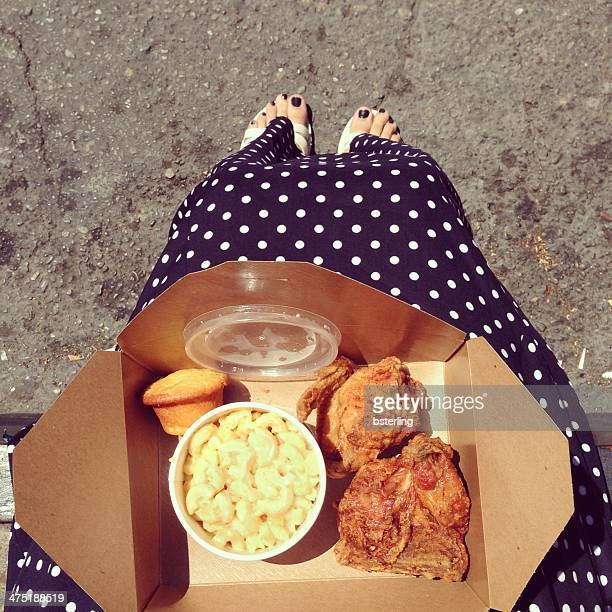USA, California, San Francisco, Woman's knees with fried chicken in box