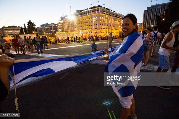 A woman with a Greek flag on her shoulders holds a giant Greek flag Unions gather outside the Parliament to protest against the ongoing voting of the...