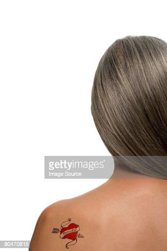 女性、ハート型のタトゥーに彼女のバック : ストックフォト