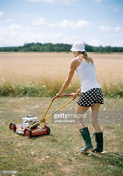 A woman with a lawnmower.