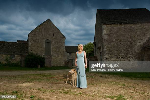 A woman with a lurcher dog in a farmyard, under a stormy sky.