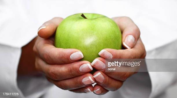 A woman with a manicure holding a green apple in her hands