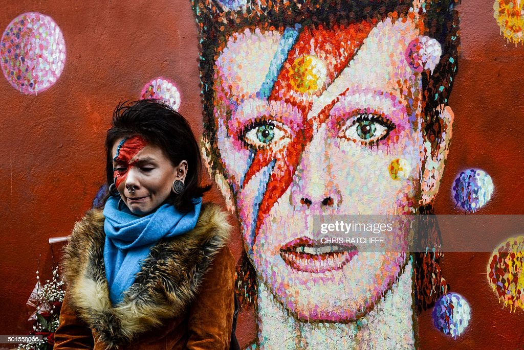 A woman with a painted face stands for a photograph in front of a mural of British singer <a gi-track='captionPersonalityLinkClicked' href=/galleries/search?phrase=David+Bowie&family=editorial&specificpeople=171314 ng-click='$event.stopPropagation()'>David Bowie</a>, painted by Australian street artist James Cochran, aka Jimmy C, following the announcement of Bowie's death, in Brixton, south London, on January 11, 2016. British music icon <a gi-track='captionPersonalityLinkClicked' href=/galleries/search?phrase=David+Bowie&family=editorial&specificpeople=171314 ng-click='$event.stopPropagation()'>David Bowie</a> died of cancer at the age of 69, drawing an outpouring of tributes for the innovative star famed for groundbreaking hits like '<a gi-track='captionPersonalityLinkClicked' href=/galleries/search?phrase=Ziggy+Stardust+-+Persona&family=editorial&specificpeople=15327884 ng-click='$event.stopPropagation()'>Ziggy Stardust</a>' and his theatrical shape-shifting style.