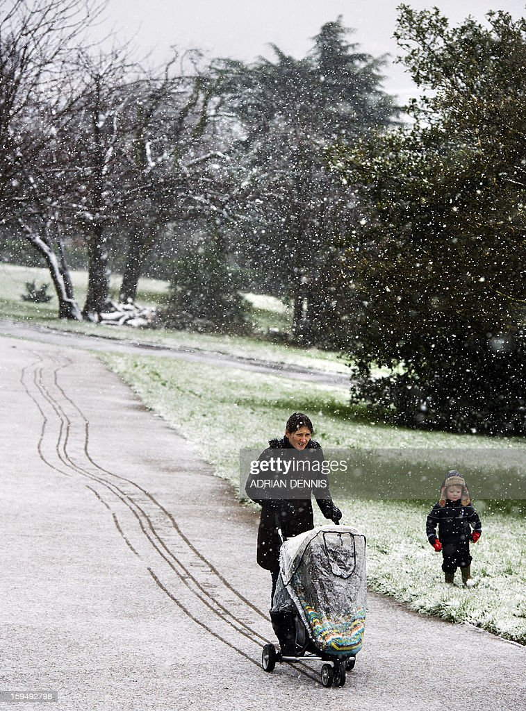 A woman with a push chair and her son walk through the snow at Alexandra Palace in London on January 14, 2013. Snow hit parts of England with up to 10cm expected to fall in some areas, prompting fears of travel chaos.